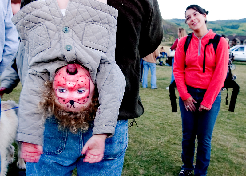 Paul Conrad/Aspen Times Weekly With a lady bug painted on her face, Lucy Meade, 3, hangs from her dad while he talks to *** at the 30th annual Snowmass Balloon Festival Saturday night September 17, 2005.