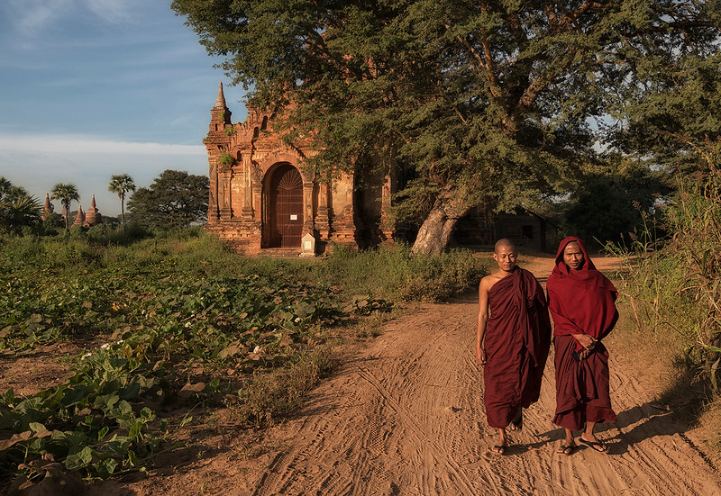 Two monks walking amongst the ancient temples of Bagan.   Bagan, Myanmar, 2017.