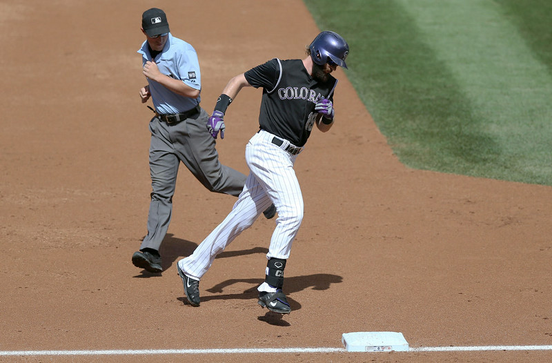 . Colorado Rockies\' Charlie Blackmon circles the bases after hitting a solo home run against the Cincinnati Reds in the second inning of a baseball game in Denver on Sunday, Aug. 17, 2014. (AP Photo/David Zalubowski)