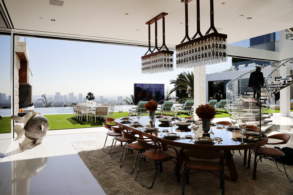 . This Thursday, Jan. 26, 2017, photo shows the indoor and outdoor dining areas at a $250 million mansion in the Bel-Air area of Los Angeles. The mansion, the most expensive home listed in the U.S., includes 12 bedroom suites, 21 bathrooms, five bars, three gourmet kitchens, a spa and an 85-foot infinity swimming pool with stunning views of Los Angeles. (AP Photo/Jae C. Hong)