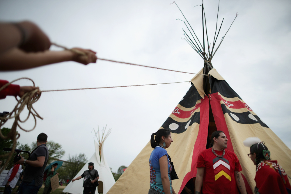 ". Native Americans from various tribes work together to erect a large tepee as part of a demonstration against the proposed Keystone XL pipeline on the National Mall April 22, 2014 in Washington, DC. As part of its ""Reject and Protect\"" protest, the Cowboy and Indian Alliance is organizing a weeklong series of actions by farmers, ranchers and tribes to show their opposition to the pipeline.  (Photo by Chip Somodevilla/Getty Images)"