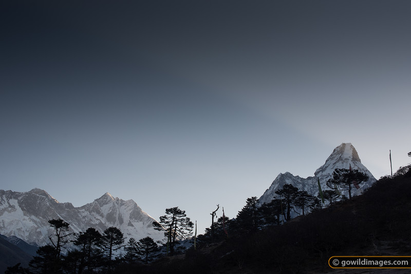Early morning light shoots over Ama Dablam, with the Tibetan prayer flags adorning the nearby ridge in Tengboche. Everest (L) catches the first light.