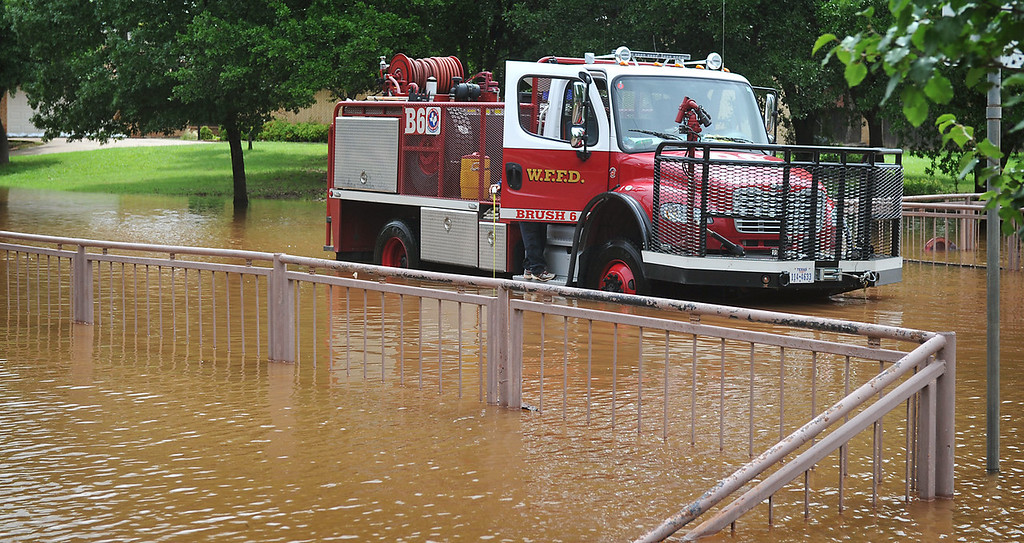 . In this May 24, 2015 photo, a Wichita Falls, Texas firefighter reaches out of his truck to measure the depth of the water on Ridgemont where the Wichita River backs into Tanglewood Lake. In the U.S., the weather system dumped record rainfall on parts of the Plains and Midwest, spawning tornadoes and causing major flooding that forced at least 2,000 Texans from their homes. (Torin Halsey/Times Record News via AP)