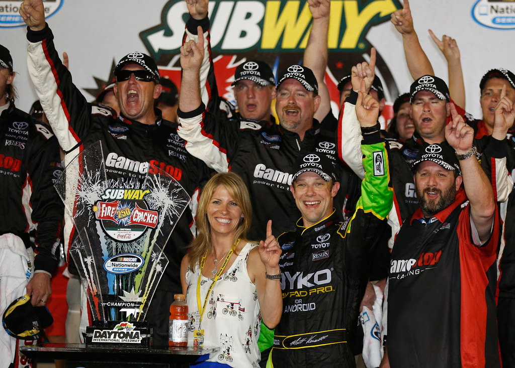 . Matt Kenseth, second from right, and his wife Katie, front left, celebrate with crew members in victory lane after winning the NASCAR Nationwide auto race at Daytona International Speedway, Friday, July 5, 2013, in Daytona Beach, Fla.  (AP Photo/Reinhold Matay)