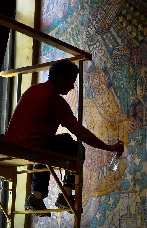 . Artist Tom Ward sprays a light layer of varnish over the mural on Tuesday morning, April 1, 2014, in preparation of the grand opening.  (Kathryn Scott Osler, The Denver Post)