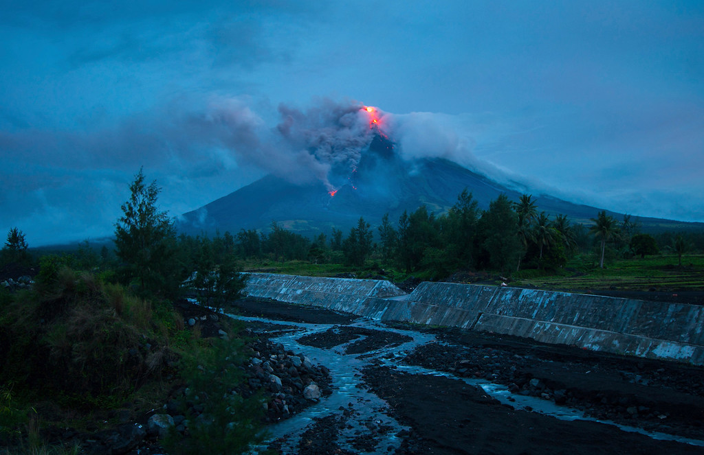 . Lava cascades down the slopes of the Mayon volcano as seen from Busay Village in Legazpi city, Albay province, 340 kilometers (210 miles) southeast of Manila, Philippines, Tuesday, Jan. 16, 2018. More than 9,000 people have evacuated the area around the Philippines\' most active volcano as lava flowed down its crater Monday in a gentle eruption that scientists warned could turn explosive. (AP Photo/Dan Amaranto)