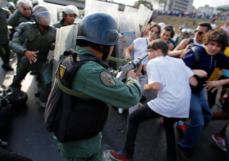 . Supporters of opposition leader Henrique Capriles scuffle with riot police as they block a highway while demonstrating for a recount of the votes in Sunday\'s election, in Caracas, April 15, 2013. Capriles called on Venezuelans to take to the streets and peacefully demand a vote recount if election authorities formally proclaim Hugo Chavez\'s chosen successor, Nicolas Maduro, as the next president.      REUTERS/Tomas Bravo