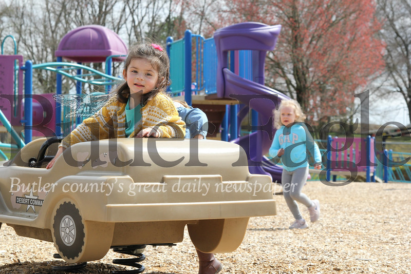 Sophie Sheppeck, 3, of Butler takes a break from piloting the desert command vehicle at Alameda Park Tuesday. Also pictured: Luna Blake, 3, climbing in vehicle behind Sheppeck &  Emery Voland, 4, in turquoise Gap shirt. Seb Foltz/Butler Eagle