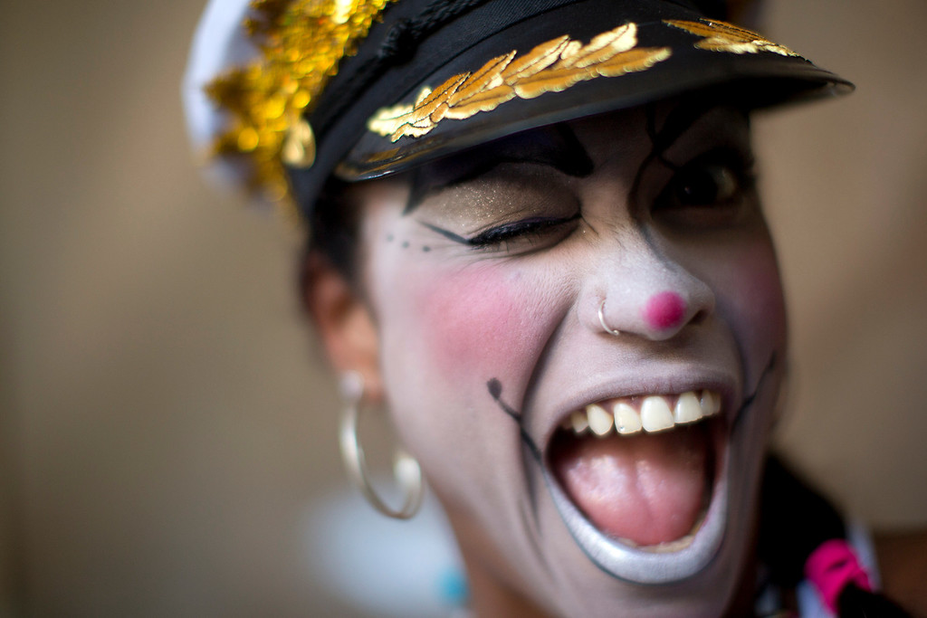 . A woman smiles for a photo at the \'Carnaval na Central\' carnival block parade, in central station, during pre-Carnival celebrations in Rio de Janeiro, Brazil, Saturday, Feb. 2, 2013. (AP Photo/Felipe Dana)