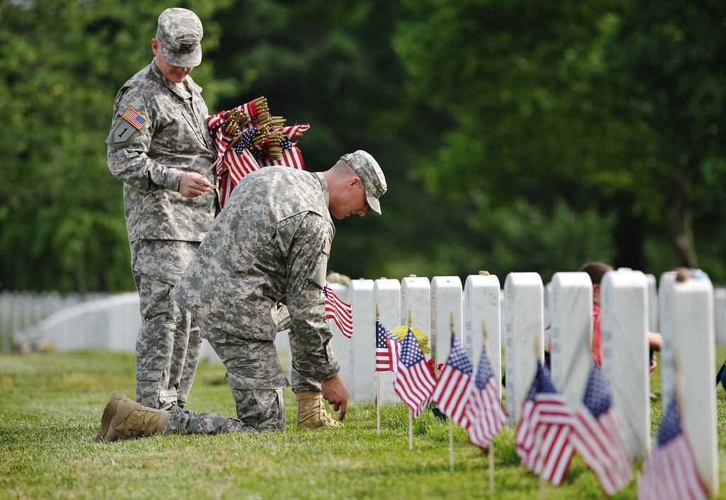 . Members of the Third US Infantry Regiment, The Old Guard, place flags in front of graves in Section 60 of Arlington National Cemetery on May 23, 2013 in Arlington, Virginia ahead of Memorial Day.  AFP PHOTO/Mandel NGAN/AFP/Getty Images
