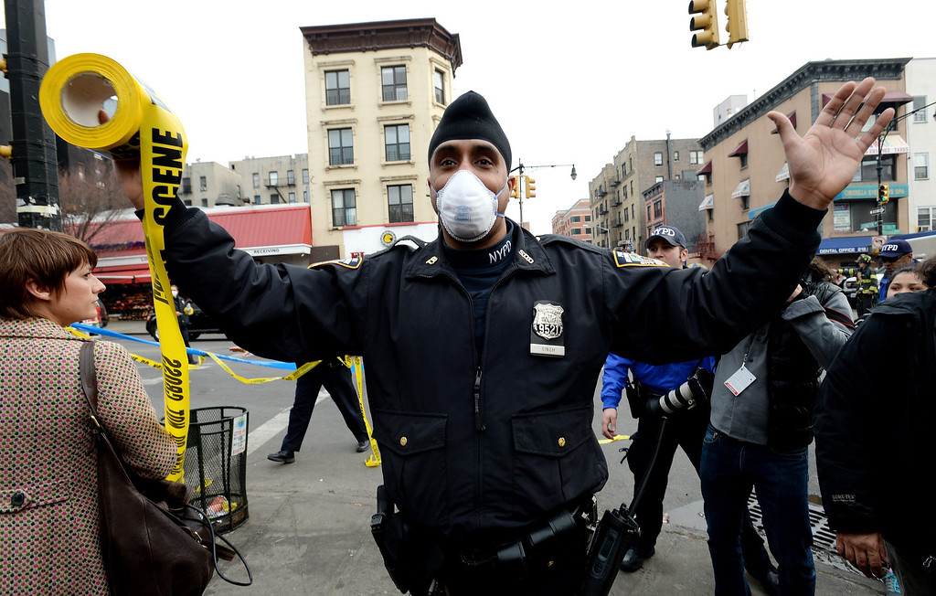 . A police officer tries to push back the crowd of people near the scene where a group of buildings were damaged by fire and a possible explosion in Harlem, New York City, New York, USA, 12 March 2014.  EPA/JUSTIN LANE