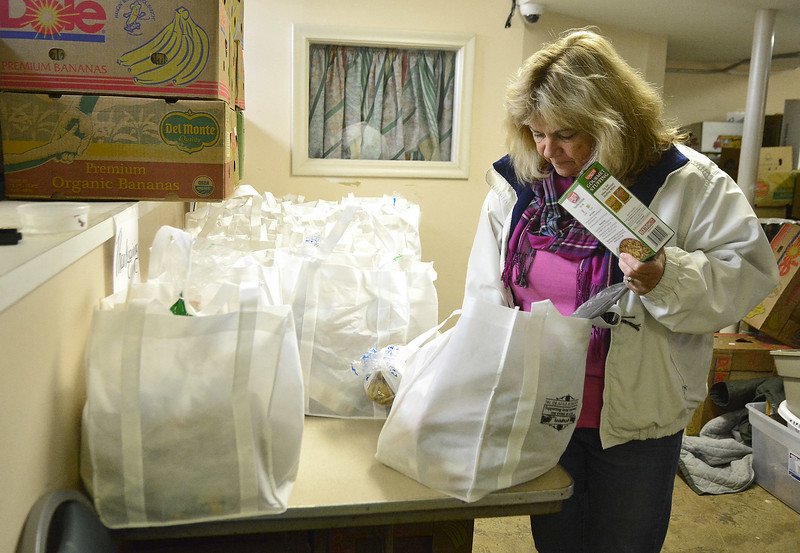 "11/22/2016 Mike Orazzi | Staff Cheryl Yetke, Director for ""Meals for the Needy"" at Zion Lutheran Church looks inside one of the bags of food that will be distributed to area needy by Tuesday of this week."