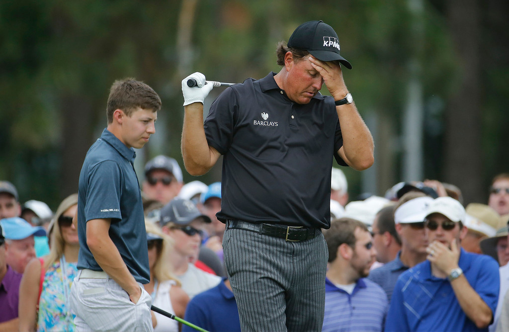 . Phil Mickelson, right, reacts to his tee shot on the eighth hole as Amateur, Matthew Fitzpatrick, England, elks by during the first round of the U.S. Open golf tournament in Pinehurst, N.C., Thursday, June 12, 2014. (AP Photo/Matt York)