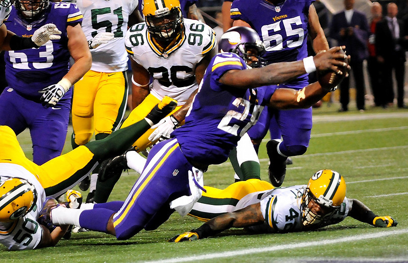 . Minnesota running back Adrian Peterson blows through Green Bay inside linebacker A.J. Hawk (50) and safety Morgan Burnett (42) to score a touchdown late in the second quarter. (Pioneer Press: John Autey)