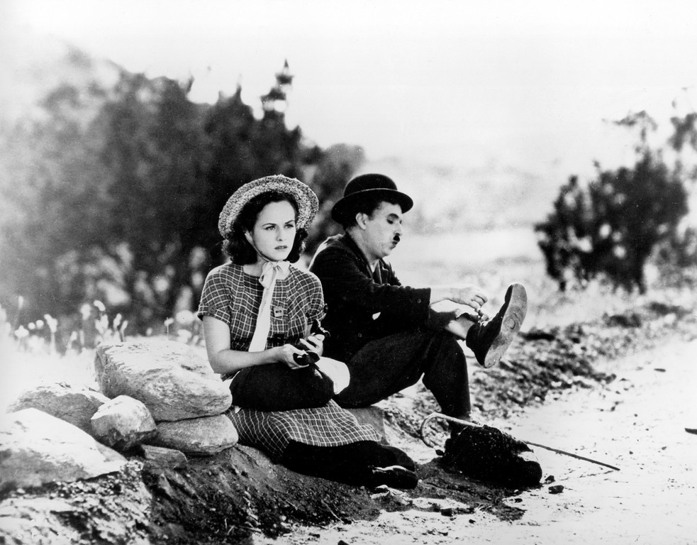 """. Actor, director and composer Charlie Chaplin and co-star Paulette Godard are shown in character sitting on the roadside in a scene from Chaplin\'s 1936 movie \""""Modern Times.\""""  (AP Photo)"""