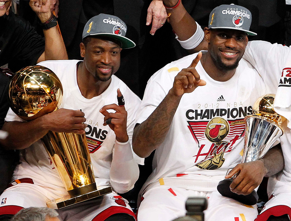 . The Miami Heat\'s Dwyane Wade holds the the Larry O\'Brien NBA Championship Trophy and LeBron James holds his most valuable player trophy after Game 5 of the NBA finals basketball series against the Oklahoma City Thunder, Friday, June 22, 2012, in Miami. The Heat won 121-106 to become the 2012 NBA Champions. (AP Photo/Lynne Sladky)
