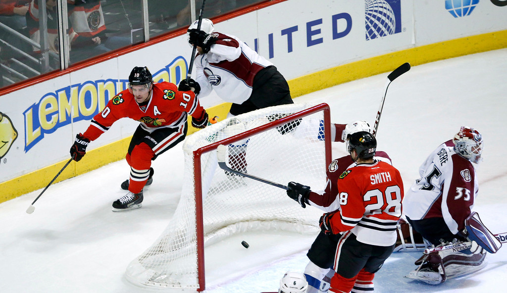 . Chicago Blackhawks left wing Patrick Sharp (10) skates behind the net after scoring on Colorado Avalanche goalie Jean-Sebastien Giguere (35) and defenseman Jan Hejda, top, as right wing Ben Smith is near during the first period of an NHL hockey game Friday, Dec. 27, 2013, in Chicago. (AP Photo/Charles Rex Arbogast)