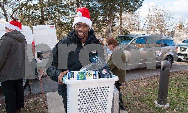 12/20/17 Wesley Bunnell | Staff Papas Dodge delivered donations to the Prudence Crandall Center on Wednesday afternoon as part of its fill the van drive held over the last several weeks. Household items were collected at the dealership such as bedding, clothes, small appliances and other household necessities clients of the center who are victims of domestic violence. Quaid Collomore from Papa's Dodge carries in a basket of items.