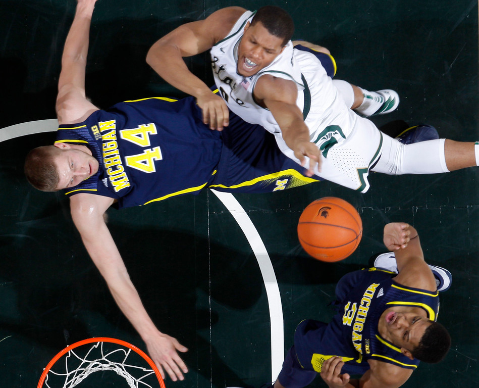 . Michigan\'s Max Bielfeldt (44) takes a charge against Michigan State\'s Marvin Clark Jr., top right, as Michigan\'s Kameron Chatman (3) watches during the first half of an NCAA college basketball game, Sunday, Feb. 1, 2015, in East Lansing, Mich. Michigan State won 76-66 in overtime. (AP Photo/Al Goldis)