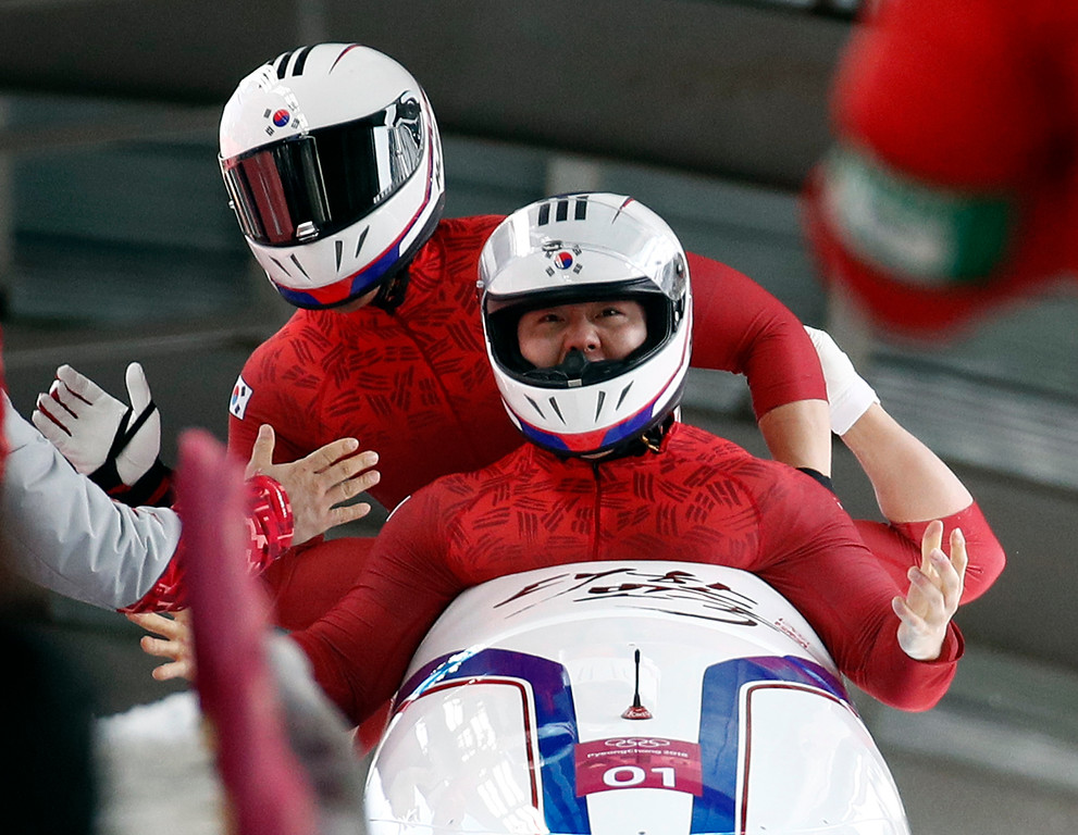 . Driver Won Yunjong, Seo Youngwoo, Jun Junglin and Kim Donghyun of South Korea celebrate tying for the silver medal during the four-man bobsled competition final at the 2018 Winter Olympics in Pyeongchang, South Korea, Sunday, Feb. 25, 2018. (AP Photo/Patrick Semansky)