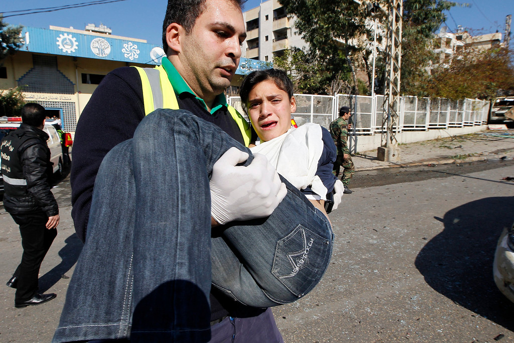 . A Lebanese rescuer carries a wounded girl from the site of explosion near the Kuwaiti Embassy and Iran\'s Chancellery center, in Beir Hassan area at southern suburbs of Beirut, Lebanon, 19 February 2014. EPA/NABIL MOUNZER