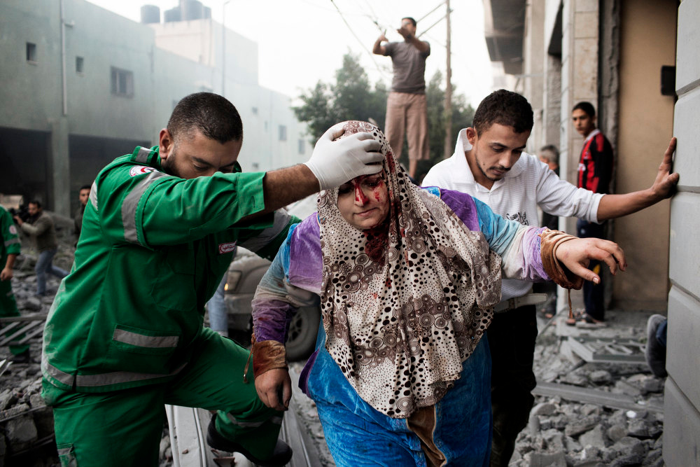 . A Palestinian woman is helped by a paramedic out of her building, damaged during an Israeli air raid on a nearby sporting centre in Gaza City November 19, 2012.   Israeli air strikes on Sunday killed 31 Palestinians in the bloodiest day so far of its air campaign on the Gaza Strip, as diplomatic efforts to broker a truce intensified.   MARCO LONGARI/AFP/Getty Images
