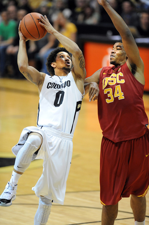 . Askia Booker of CU shoots on Eric Wise of USC during the second half of the January 10, 2013 game in Boulder.   Cliff Grassmick/Daily Camera