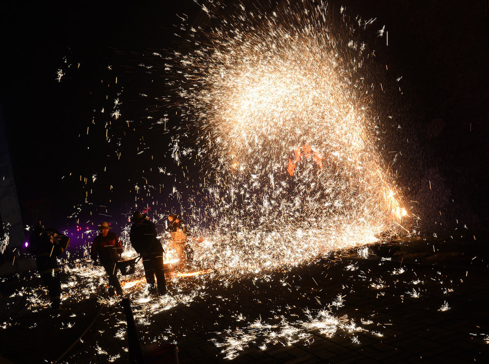 Description of . This photo taken on February 24, 2013 shows Chinese blacksmiths throwing molten metal against a cold stone wall to create sparks during the Lantern Festival which traditionally marks the end of the Lunar New Year celebrations, in Nuanquan, Hebei Province. For over 300 years, the village, which is famous for its blacksmith skills, has maintained the tradition which they considered a cheaper alternative than buying fireworks during the Lantern Festival.      MARK RALSTON/AFP/Getty Images