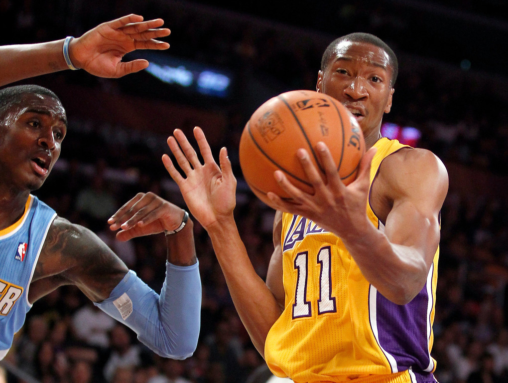 . Los Angeles Lakers guard Wesley Johnson (11) pulls down a rebound against Denver Nuggets forward Quincy Miller in the first quarter during an NBA preseason basketball game Sunday, Oct. 6, 2013 in Los Angeles.  (AP Photo/Alex Gallardo)