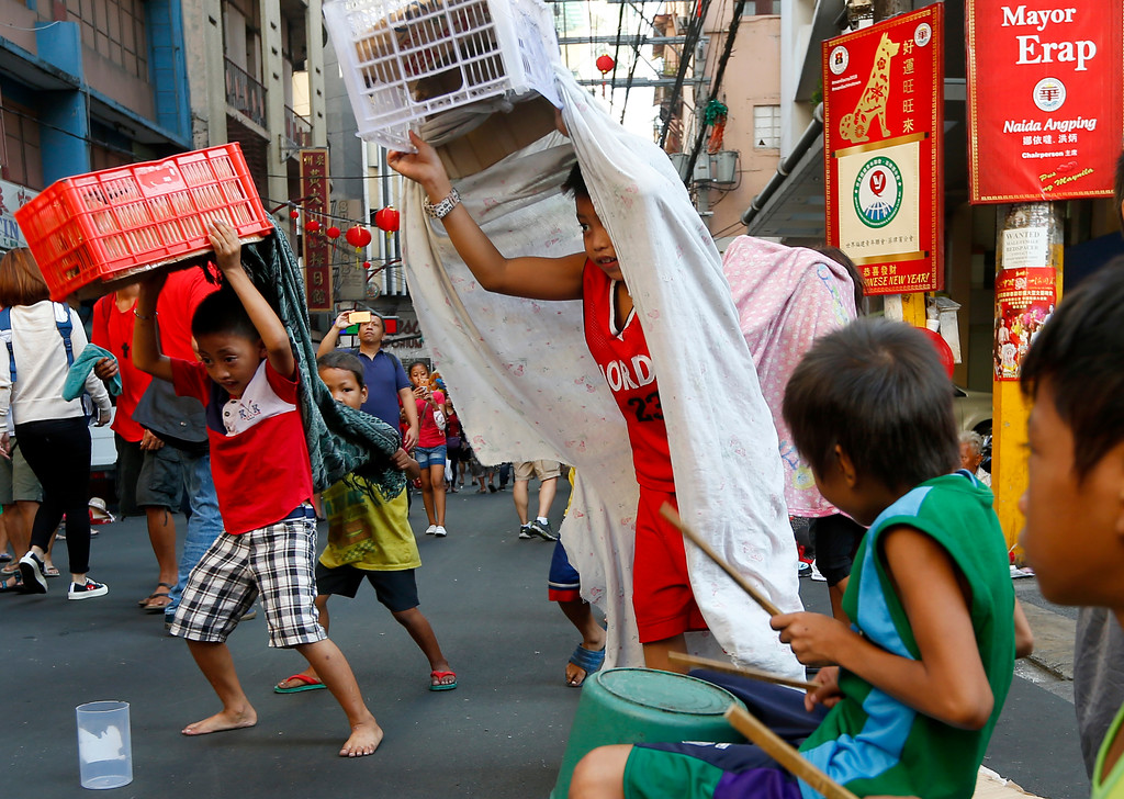 . Enterprising Filipino children use improvised lion costumes as they perform lion dance in celebration of the Chinese Lunar New Year Friday, Feb. 16, 2018 at Manila\'s Chinatown district in Manila, Philippines. This year is the Year of the Dog in the Chinese Lunar calendar. (AP Photo/Bullit Marquez)