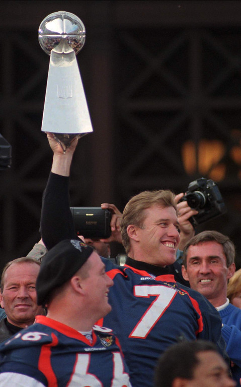 . Denver Broncos quarterback John Elway (7) holds the Lombardi Trophy as team owner Pat Bowlen, left, enter Tom Nalen (66), and coach Tom Shannahan watch on Tuesday, Jan. 27, 1998 during a rally at the Denver City and County Building to celebrate the Broncos victory in the Super Bowl.(AP Photo/Joe Mahoney)
