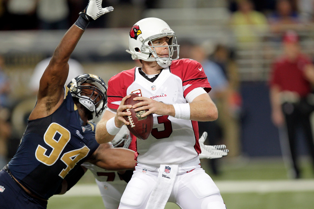 . St. Louis Rams defensive end Robert Quinn, left, sacks Arizona Cardinals quarterback Carson Palmer for an 8-yard loss and causing Palmer to fumble during the fourth quarter of an NFL football game on Sunday, Sept. 8, 2013, in St. Louis. The Rams recovered the fumble. (AP Photo/Tom Gannam)