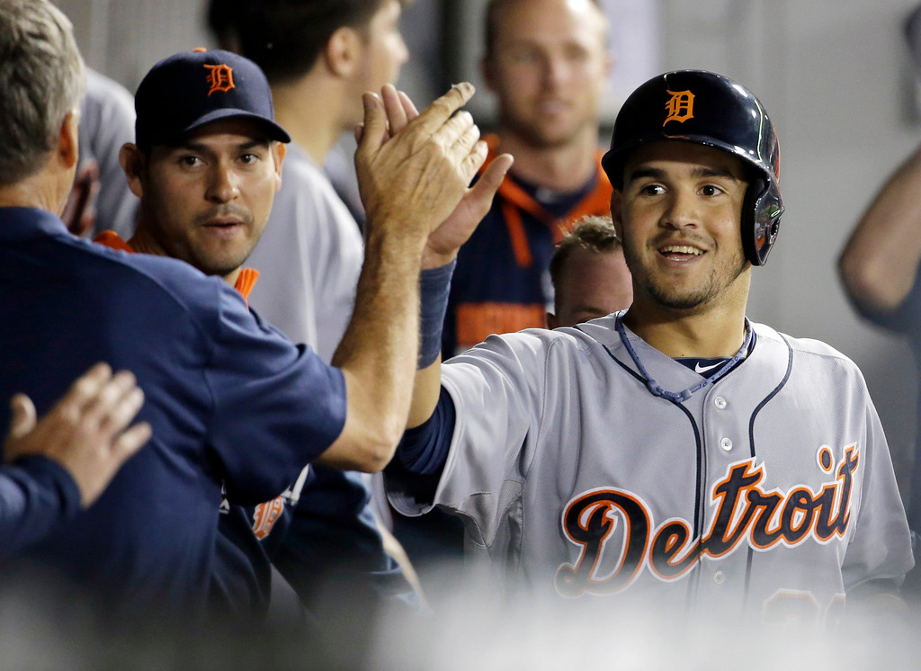 . Detroit Tigers\' Eugenio Suarez, right, celebrates with teammates after scoring on a two-run single hit by Miguel Cabrera during the eighth inning of a baseball game against the Chicago White Sox in Chicago on Thursday, June 12, 2014. (AP Photo/Nam Y. Huh)