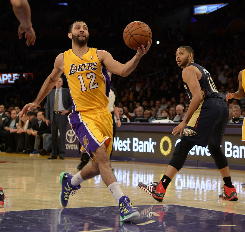 . Los Angeles Lakers point guard Kendall Marshall (L) goes up for a shot as New Orleans Pelicans shooting guard Eric Gordon (R) looks on during the first half of their NBA game at the Staples Center in Los Angeles, California, USA, 04 March 2014.  EPA/MICHAEL NELSON