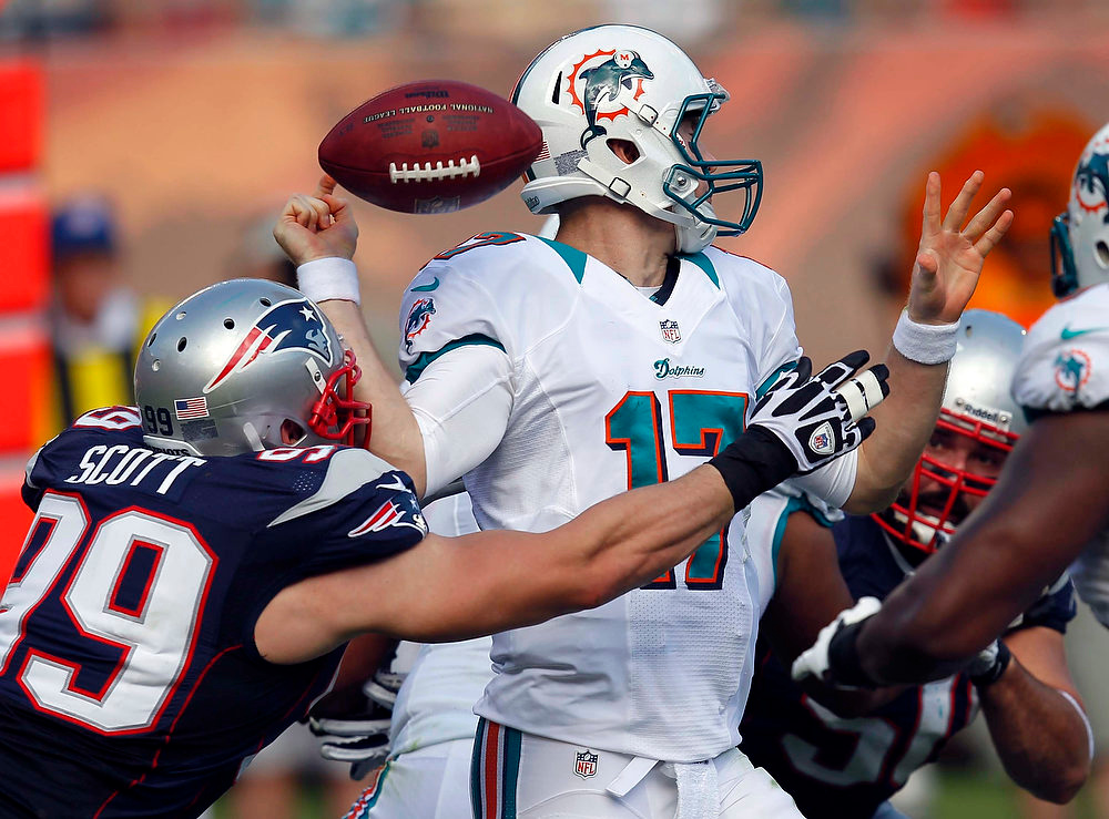 Description of . Miami Dolphins quarterback Ryan Tannehill (17) fumbles the ball after being hit by New England Patriots defensive end Trevor Scott (99) during the first half of an NFL football game, Sunday, Dec. 2, 2012 in Miami. (AP Photo/Wilfredo Lee)