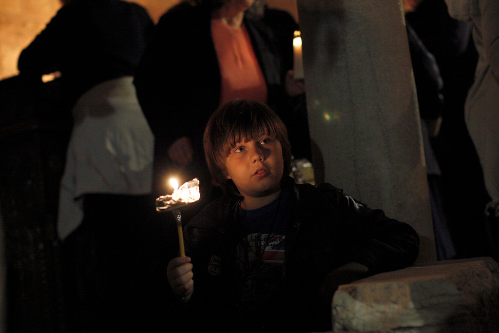 . A child carries the Holy Fire during an Easter Mass at the church of Agii Anargyri in Athens, late Saturday, April 19, 2014. The Holy Fire is brought in Greece every year from the church of the Holy Sepulcher in Jerusalem, traditionally believed to be the burial site of Jesus Christ . (AP Photo/Kostas Tsironis)