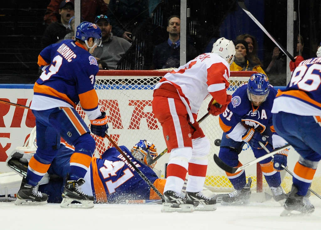 . Detroit Red Wings center Pavel Datsyuk (13) shoots the puck past a diving New York Islanders goalie Jaroslav Halak (41) to score as Islanders defenseman Travis Hamonic (3) and center Frans Nielsen (51) try to defend during the second period of an NHL hockey game Sunday, March 29, 2015, in Uniondale, N.Y. (AP Photo/Kathy Kmonicek)