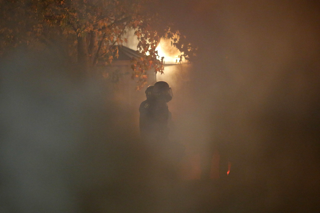 . A police officer is seen through a cloud of teargas and smoke during a demonstration over recent grand jury decisions in police-involved deaths on Sunday, Dec. 7, 2014, in Berkeley, Calif. (Stephen Lam/Getty Images)