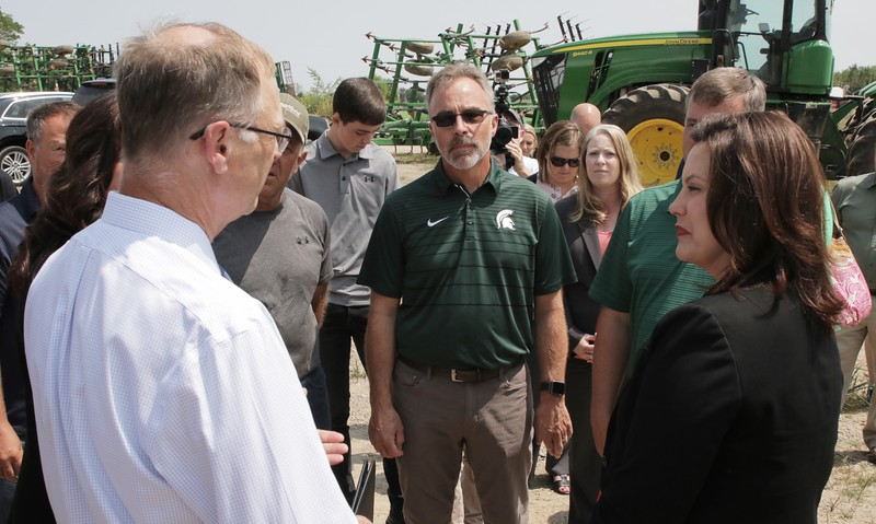 Gov. Gretchen Whitmer, Eaton County farmer Duane Smuts, MFB Director Jeff Sandborn listen to MDARD Director Gary McDowell (right to left).