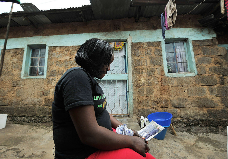 """. Eunice Khavetsa, 27, looks at a picture with an image of her late husband, Kenyan security guard Maurice Adembesa, at her home in one of Nairobi\'s crowded suburbs as she recounts seeing her late husband\'s body following the massacre of 67 people at the upmarket Wesgate mall a year ago on September 21. \""""Our lives have changed forever,\"""" said Ombisa\'s widow Eunice Khavetsa, who now cares for her nine-year old son and seven-year old daughter alone. TONY KARUMBA/AFP/Getty Images"""