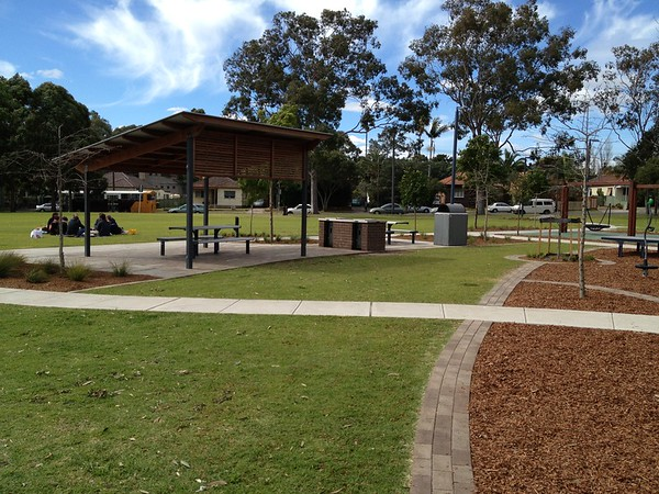 steel post and timber beam shade structure with steel roof over bbq table and benches and bbq and brick edging