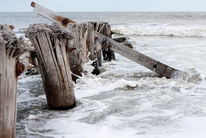Waves crash along the jetty.