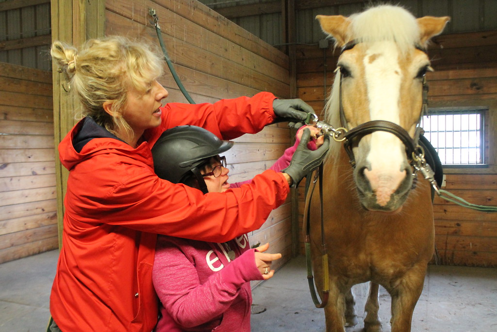 . Kathy Habat,  a client  Willoughby Branch learns how to put reins on a horse with help from Fieldstone Farm volunteer Lindsey Nazelli  before riding as part of the equine therapy sessions.  Kristi Garabrandt - The News-Herald