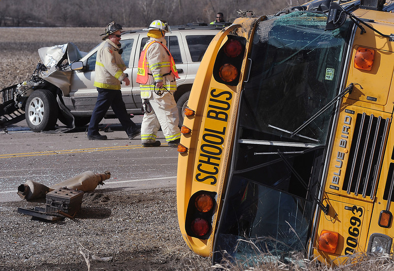 . Emergency personnel walk the scene where a school bus carrying around two dozen elementary school children overturned, Friday, April 5, 2013, near Wadsworth, Ill. Authorities say one person has died and more than three dozen people are injured. (AP Photo/The Kenosha News, Bill Siel)