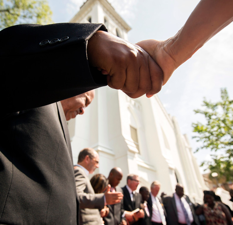 . People hold hands during a prayer service by the National Clergy Council outside the Emanuel AME Church, Saturday, June 20, 2015  in Charleston, S.C. Clergy from around the country led prayers and words of hope to the people in attendance. (AP Photo/Stephen B. Morton)