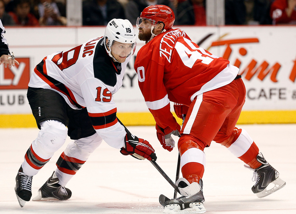 . New Jersey Devils center Travis Zajac (19) and Detroit Red Wings left wing Henrik Zetterberg (40) battle for the puck in the second period of an NHL hockey game in Detroit, Friday, Nov. 7, 2014. (AP Photo/Paul Sancya)