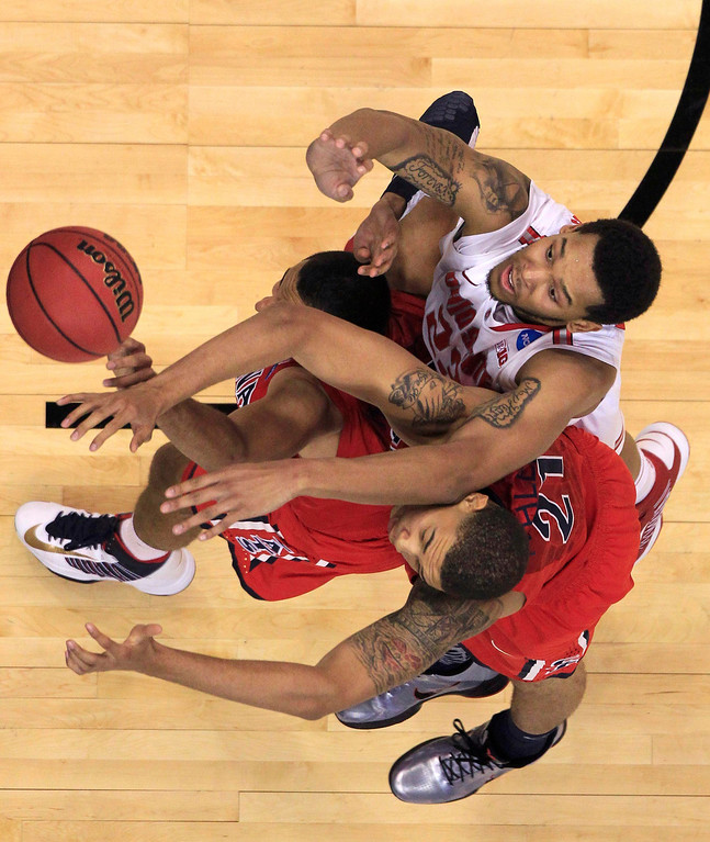 . Ohio State Buckeyes center Amir Williams (top, R) fights for a rebound with Arizona Wildcats\' Brandon Ashley (21) and Grant Jerrett (33) in the second half of their West Regional NCAA men\'s basketball game in Los Angeles, California March 28, 2013. REUTERS/Lucy Nicholson