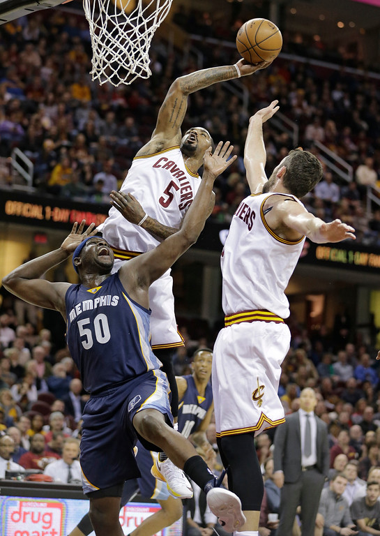 . Cleveland Cavaliers\' J.R. Smith (5) shoots over Memphis Grizzlies\' Zach Randolph (50) in the first half of an NBA basketball game Tuesday, Dec. 13, 2016, in Cleveland. Kevin Love is on the right. (AP Photo/Tony Dejak)