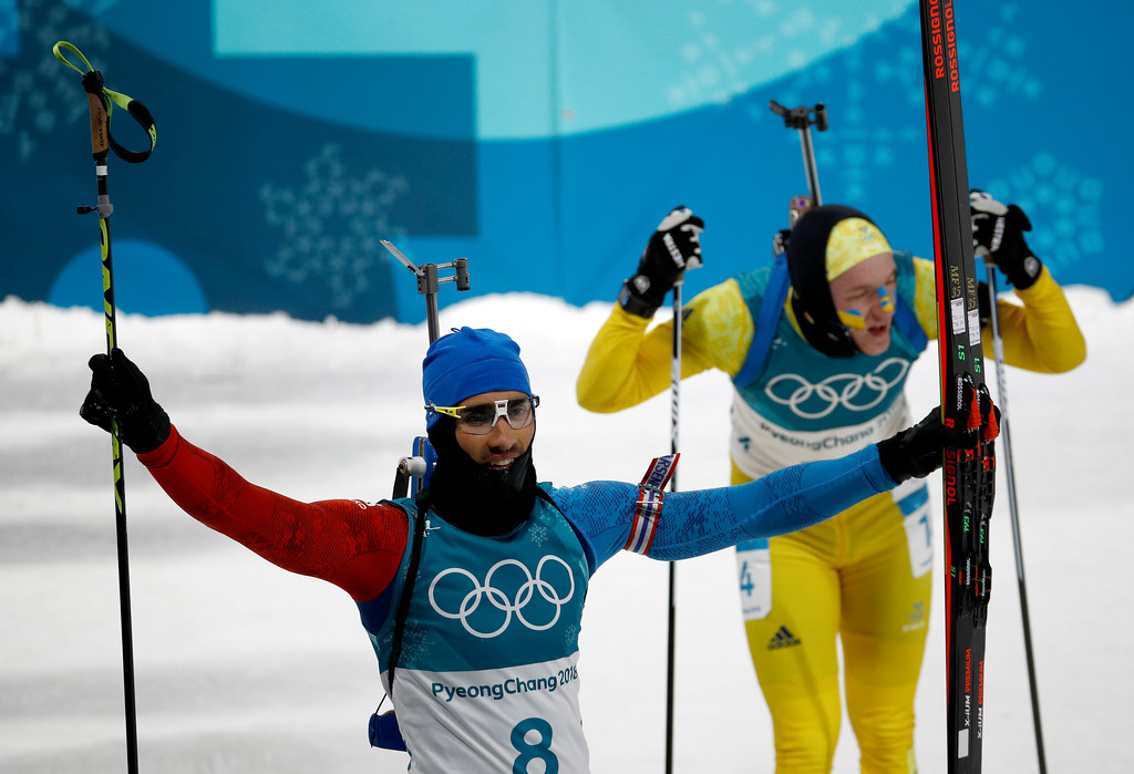 . Gold medalist Martin Fourcade, of France, 8, and Silver medalist Sebastian Samuelsson, of Sweden, 14, rest in the finish area of the men\'s 12.5-kilometer biathlon pursuit at the 2018 Winter Olympics in Pyeongchang, South Korea, Monday, Feb. 12, 2018. (AP Photo/Charlie Riedel)