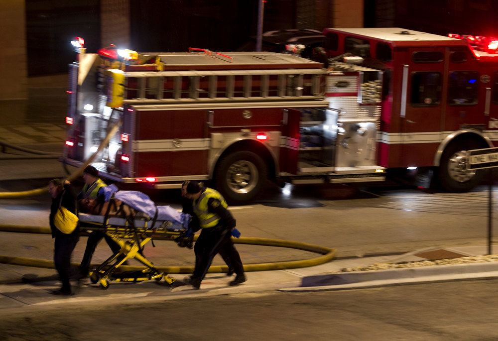 . Emergency personnel wheel an injured victim from the scene of a gas explosion and massive fire Tuesday night, Feb. 19, 2013 at the Country Club Plaza in Kansas City, Mo. A car crashed into a gas main in the upscale Kansas City shopping district, sparking a massive blaze that engulfed an entire block and caused multiple injuries, police said. (AP Photo/The Kansas City Star, Tammy Ljungblad)